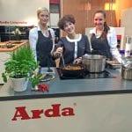 Messehostessen hinter einer Musterküche des Herstellers Arda