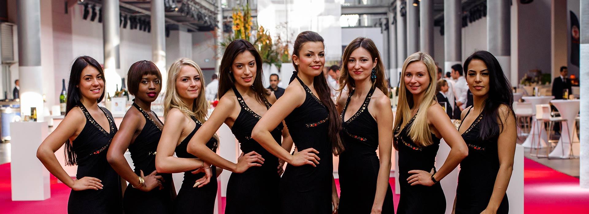 Acht Messehostessen im schwarzen Abendkleid